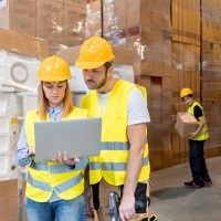 warehouse-workers-consult-delivery-plans-using-lap-3E6PBVC.jpg